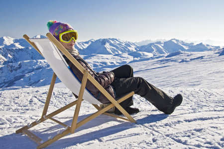 Girl sunbathing in a deckchair on the side of a ski slope, snowy mountain landscape Banco de Imagens