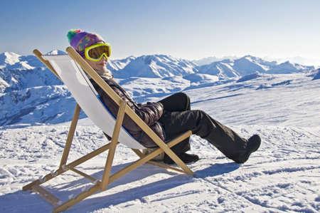 Meisje zonnebaden in een ligstoel aan de kant van een skipiste, besneeuwde berglandschap