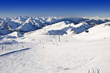 skiers: Snowy ski slope with skiers in the Alps, France