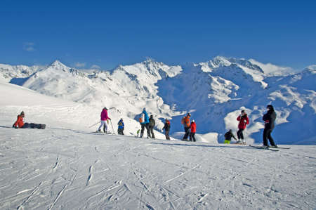Skiers at the beginning of a ski slope, snowy peaks of the Alps, France