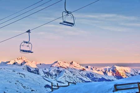 montañas nevadas: Telesilla y montañas nevadas en el fondo al atardecer Foto de archivo