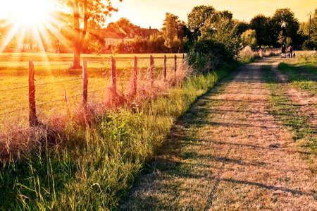 paisaje rural: paisaje rural con un campo y un pueblo en la puesta del sol