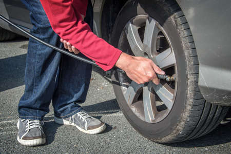 air pressure: Driver checking air pressure and filling air in a tire of a car Stock Photo