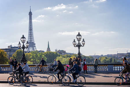 People on bicycles and pedestrians enjoying a car free day on Alexandre III bridge in Paris, France Редакционное