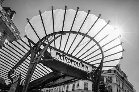 Metropolitain art nouveau sign with a glass roof in Paris France, black and white