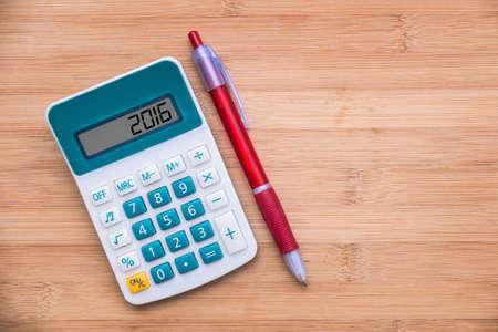 calculadora: 2016 escrito en una calculadora y un l�piz sobre fondo de madera