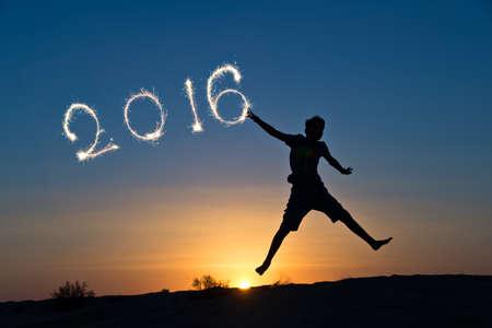 nouvel an: 2016 �crite avec des �tincelles, silhouette d'un gar�on de sauter dans le soleil Banque d'images