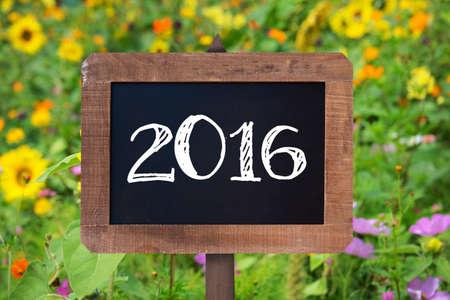 jardines con flores: 2016 escrito en un cartel de madera, los girasoles y flores silvestres en el fondo Foto de archivo
