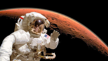 exploration: Close up of an astronaut in outer space, planet Mars in the background.