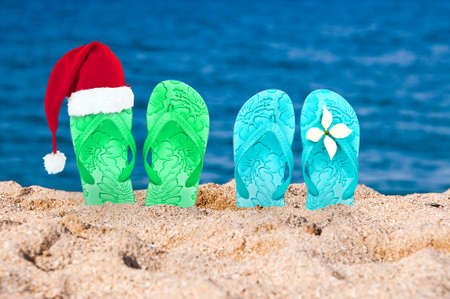 christmas present: Christmas hat on flip flops in the sand of a beach