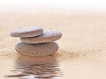 balance life: Zen stone stack and sand, water reflections