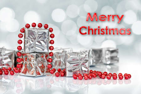 christmas beads: Small Christmas gifts in shiny silver paper and red tinsel beads ornament