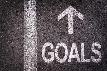 Word Goals and an arrow written on an asphalt road background