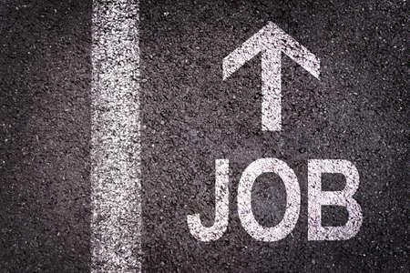 straightforward: Word job and an arrow written on an asphalt road background