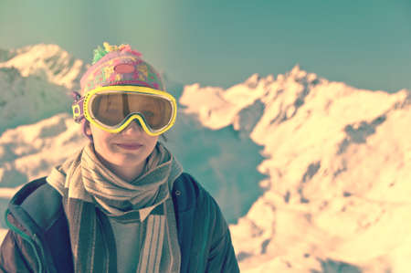 mountainscape: Portrait of a girl in front of a snowy mountainscape, vintage process Stock Photo