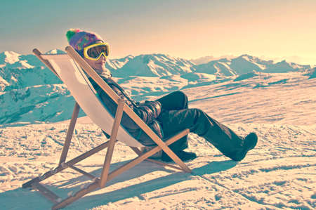 Girl sunbathing in a deckchair on the side of a ski slope, vintage process