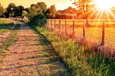 fence: Countryside landscape with a field and a village in the sunset Stock Photo