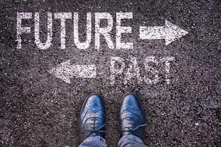 Voeten en woorden toekomst en verleden geschilderd op een asfaltweg