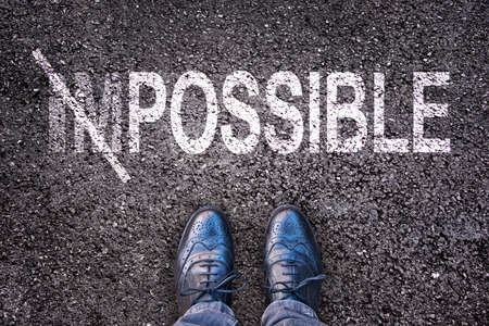 Changing the word impossible on possible on an asphalt road with feet