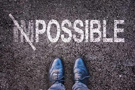 Het veranderen van het woord onmogelijk op mogelijk op een asfaltweg met voeten Stockfoto