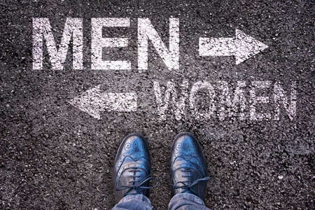 challenging sex: Feet and words men and women painted on an asphalt road Stock Photo