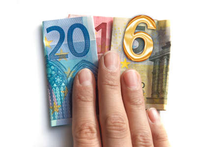 holiday budget: 2016 written with euros bank notes in a hand isolated on white background