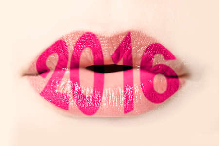 mouth kiss mouth: 2016 written with pink lipstick on girl lips Stock Photo