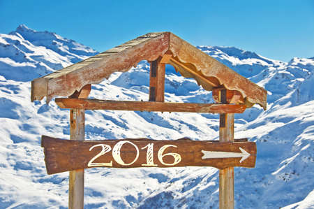mountainscape: 2016 written on a wooden direction sign, snow mountain landscape on the background