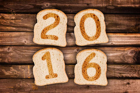 new message: 2016 greeting card toasted slices of bread on wooden planks background