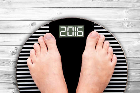 2016 feet on a weight scale on white wooden floor background Foto de archivo