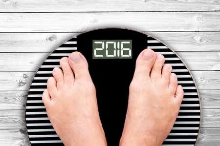 sano: 2016 pies en una escala de peso sobre fondo blanco suelo de madera Foto de archivo