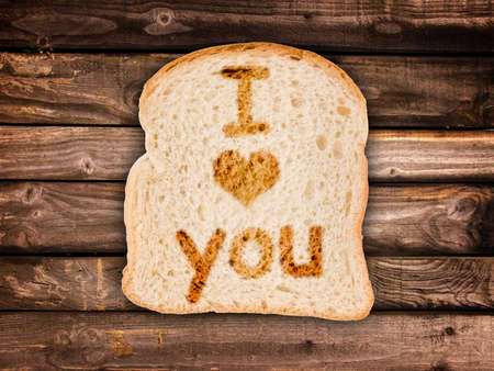 i love u: Message I love you written on a toasted slice of bread, on wooden planks background