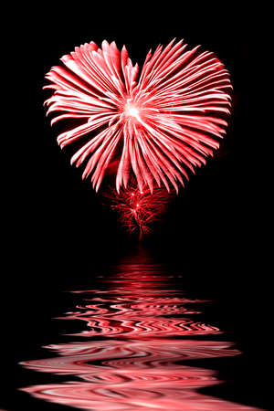 love shape: Red firework in the shape of a heart, water reflections Stock Photo
