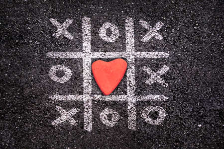 romance strategies: Happy Valentines day card, Tic tac toe game on the ground, xoxo and stone in the shape of a heart