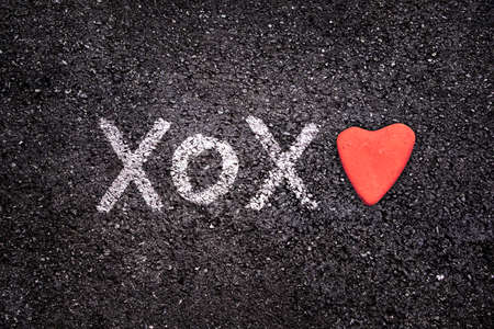 xoxo: Happy Valentines day card, xoxo on the ground and stone in the shape of a heart Stock Photo