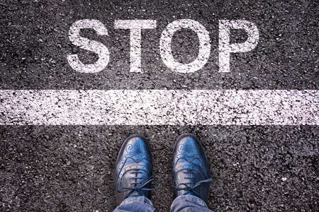 Word Stop written on an asphalt road with legs and shoes Standard-Bild