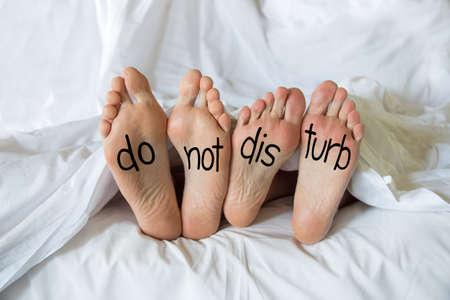 침대에서 한 쌍의 발에 쓰는 것을 방해하지 마라. 스톡 콘텐츠