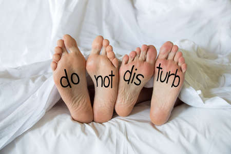 Niet storen geschreven op de voeten van een paar in een bed Stockfoto