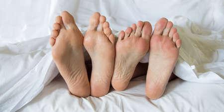 enamorados en la cama: Pies de una pareja en una cama Foto de archivo