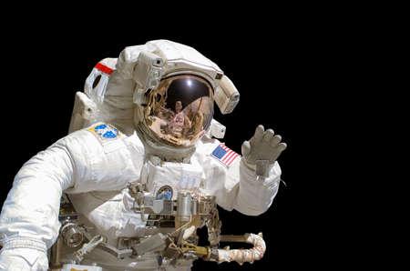 personas saludando: Cerca de un astronauta aislado en el fondo negro Foto de archivo