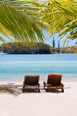 loungers: Loungers under a palm tree on a tropical beach, Isle od Pines, New Caledonia Stock Photo