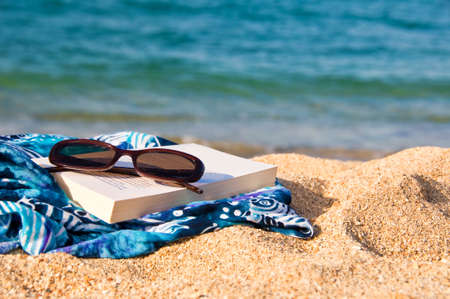 pareo: Book, sunglasses and pareo on a beach Stock Photo