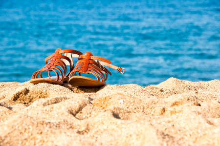 up close: Sandals on the sand of beach, blue water background