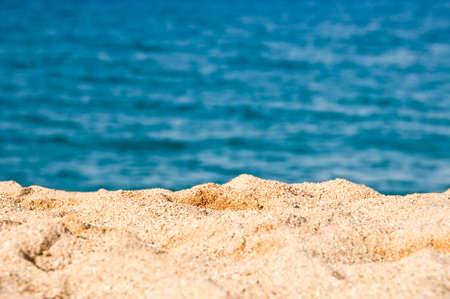 Close up on the sand of a beach, blue sea water in the background