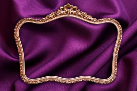 gold frame: Antique golden photo frame, purple fabric background