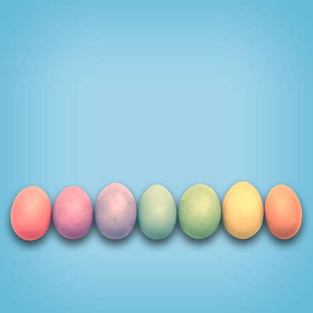 cicuta: Huevos de Pascua en colores pastel alineados, fondo azul
