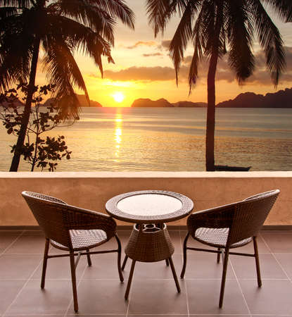 resort beach: Table and chairs on a terrace, view on a tropical beach at sunset Stock Photo