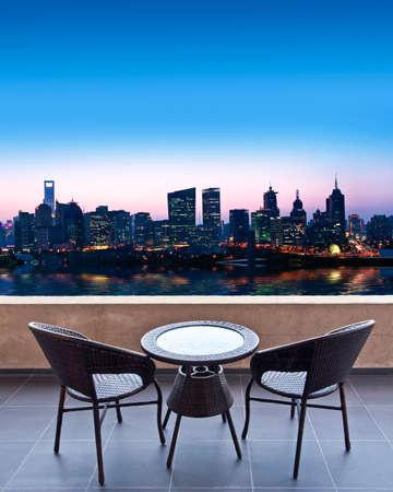 Tafel en stoelen op een terras, uitzicht op een stad (Shanghai) 's nachts Stockfoto