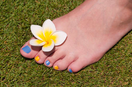 girl feet: Close up on woman bare foot with frangipani flower, in the grass Stock Photo