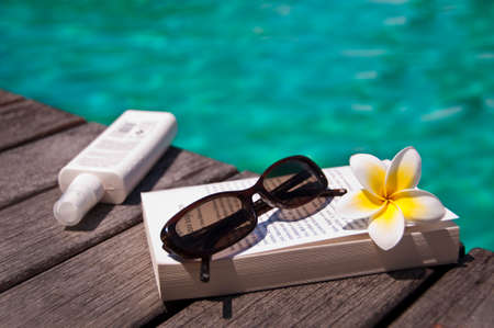 Book and sunglasses, blue water background